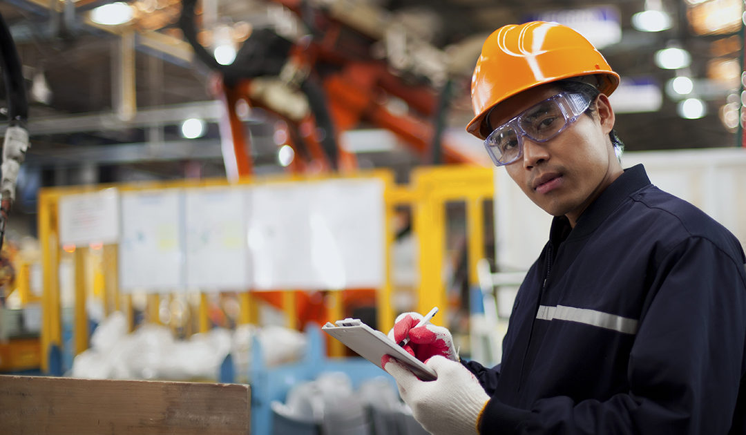 Asian industrial engineer writing down information