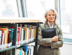 Mature woman standing next to the bookshelves