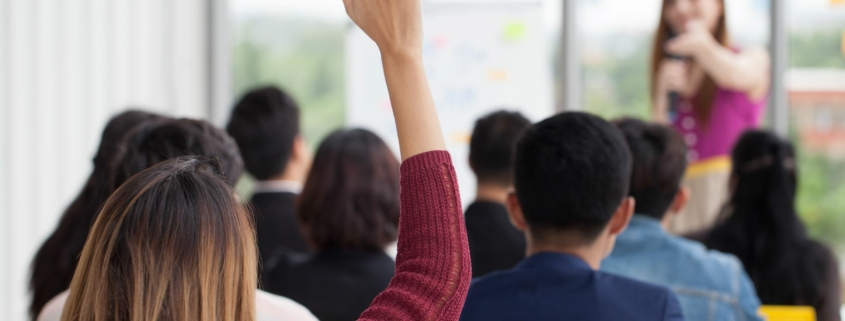 Woman raises hand during workplace training